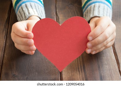 children's hands with red heart, concept of care, love and devotion