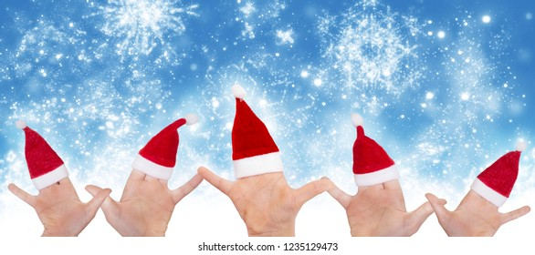 Children's hands with Santa hats in front of starry sky, christmas card