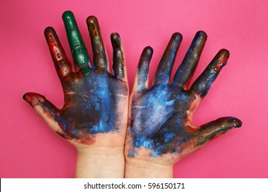 Children's hands are stained with a multicolored paint on a pink background.