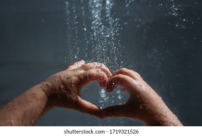 Children's hands under a stream of water on a dark background. Drops are highlighted. Copy space