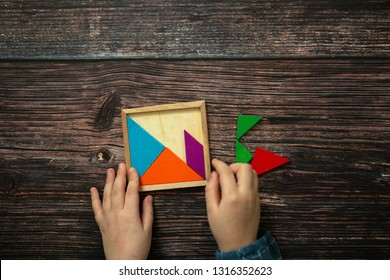 children's hands and wooden puzzle game on a wooden background. Top view The concept of independent children's educational toys in school. thinking