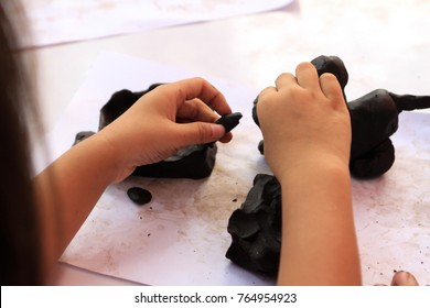 Children's hands working with clay on the wooden table with white paper. School and homeschool art activity.