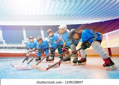 Children's hockey team line up on ice rink