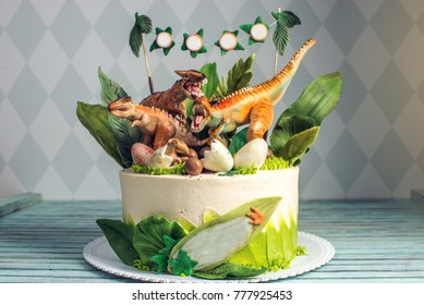 Children's holiday white cake decorated with mastic figurines of dinosaurs in the Jurassic period jungle. Concept ideas desserts for kids