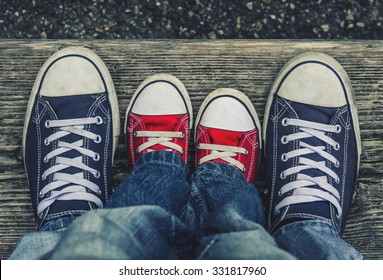 Children's legs and feet in shoes adult sneakers with each other.
