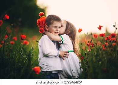 Children's love, a little boy and a girl, amicably spend time, laugh and smile, and kiss in the flowering field of poppies