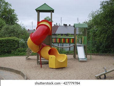 Childrens multi colors playground in public park. Bridge, stairs, slide, platforms. Place for games and sports activities.