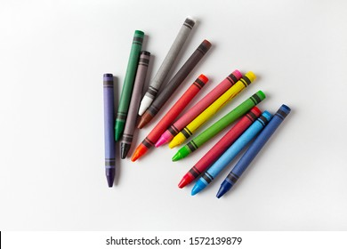 children's multi-colored wax crayons for drawing on a white landscape sheet