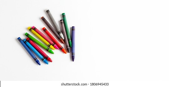 children's multi-colored wax crayons for drawing on a white landscape sheet with free space for text on the right side. Left hand drawing concept