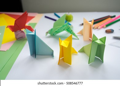 Children's  origami  wolf's and bird's from colored paper. Working place is decorated with leaves of color paper, scissors, colored wood ladybugs and pencils.