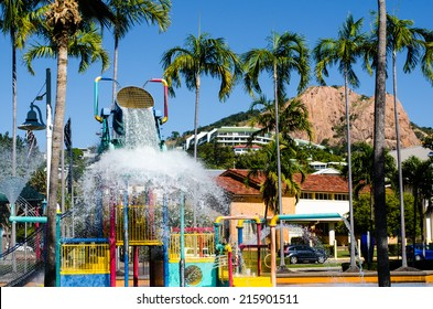 Children's outdoor aquatic playground with cascading water bucket. Townsville, Queensland, Australia. Castle Hill is in background of picture.