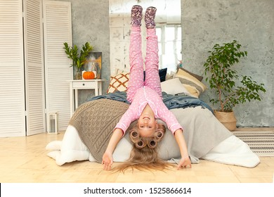 Children's pajama party. A teenage girl in pink pajamas is fooling around on the bed, hanging upside down and upside down.