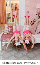 Children's pajama party. A teenage girl in pink pajamas, makeup, and pink curlers is lying upside down on the bed.