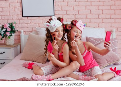 Children's pajama party. A teenage girl in pink pajamas, with makeup and pink curlers on the bed takes a selfie.