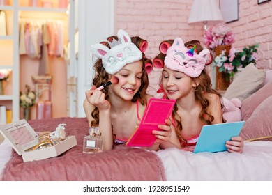 Children's pajama party. A teenage girl in pink pajamas, with makeup and pink curlers on the bed with makeup brushes is making up.