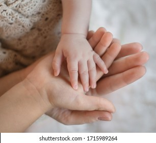children's palm in another children's palm in an adult hand. hand in hand. tenderness. close-up