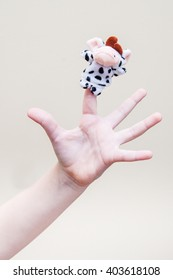 Children's palm with a toy cow on the index finger