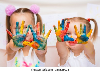 Children's palms painted with colored inks, against children