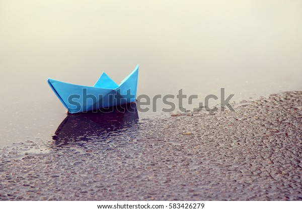 children's paper boat in a puddle of spring / waiting for favorable wind
