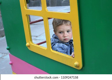 Children's phobias at the beginning of socialization. The kid looks sadly out the window. A sad child sits alone in a children's house on the playground.