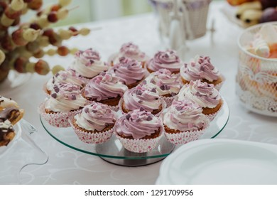Children's pink cake with cupcakes on a wooden background with lace fabric in vintage style. Cake for girl on birthday party, candybar. Copy space, close up
