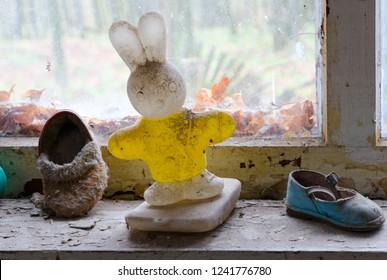 Children's plastic toy and shoes on windowsill in abandoned kindergarten in destroyed village Kopachi (10-km Chernobyl NPP alienation zone), Ukraine