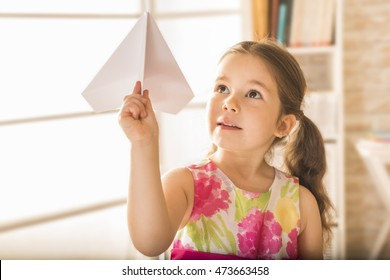 Children's play concept. Adorable little girl playing with origami paper airplane