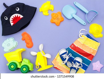 children's play set for sand, playing in the sandbox, on the sea or in the park. Panama, shorts and a bright plastic set of toys for kids: molds for modeling, rakes and shovel on a purple background