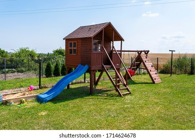 Childrens playground by the house garden, visible wooden house, beautiful spring day.