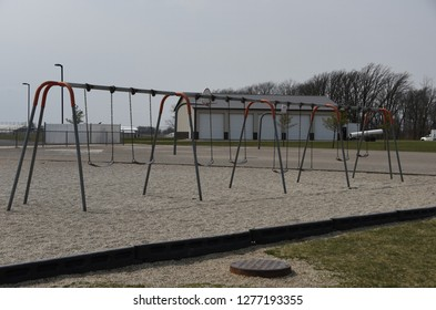 children's playground equipment swing set multiple numerous swings in a long roll with gravel, toys, play