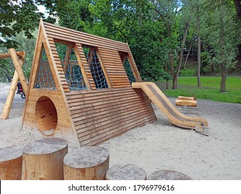 Children's playground equipped with wooden swings and slides. A modern children's slide made of wood and natural materials.