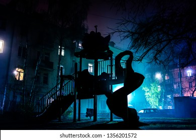 Children's playground at night in the fog