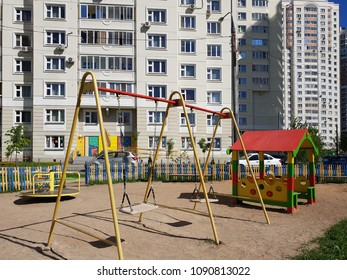 children's playground with swings in courtyard of residential building in the city, Russia