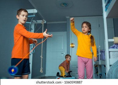 Childrens playing with yo-yo toy. Home plays.