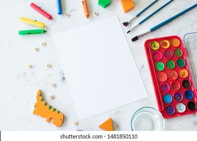 Children's Preschool Art Supplies surrounding Blank Paper Mockup Concept Flat Lay for Montessori Class