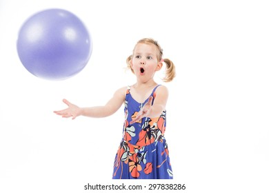 Children's real emotions. Little girl catching a ball isolated on white background.
