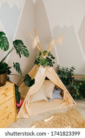 """children's room: live tropical plants with large leaves, soft pillows, a teepee. interior elements: wooden inscription """"baby"""", balloons. example of decorating a play area and recreation area"""
