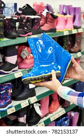 Children's rubber boots in the hands of the buyer in the store