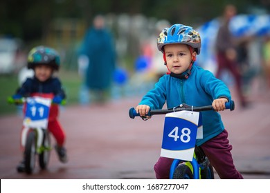 Children's runbike competition. The boy in the helmet is ahead of the opponent. Kids cycling competition in Almaty. Kazakhstan