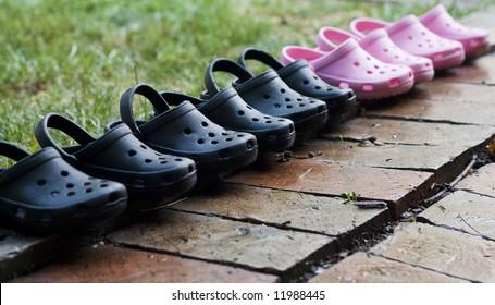 Children's sandals on wet brick sidewalk.