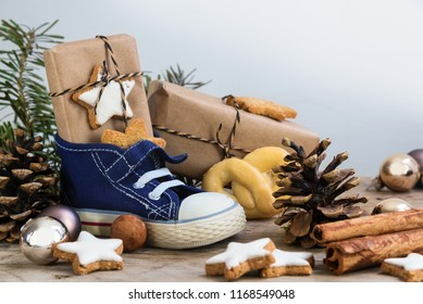 Children's shoe with sweets, gifts and christmas ornaments on rustic wood, german text Am 6. Dezember ist Nikolaustag, meaning  St. Nicholas Day December 6th, selected focus, narrow depth of field