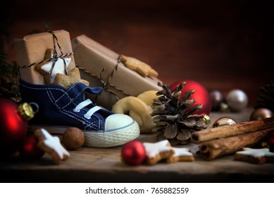Children's shoe with sweets and gifts for St. Nicholas Day on December 6th at Christmas time on rustic wood, traditional custom in Germany called Nikolaus, selected focus, narrow depth of field