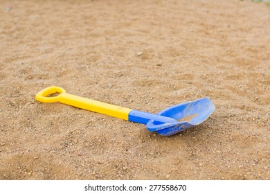 Children's shovel lying on the sand on the playground