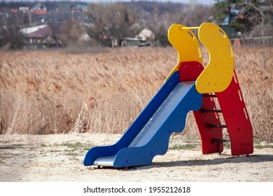 children's slide located in a deserted place. dried grass field. empty playground. sunny day.