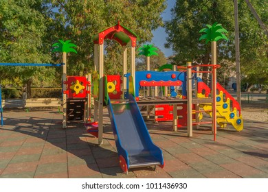 Children's slide and toy house with palm trees, outdoor