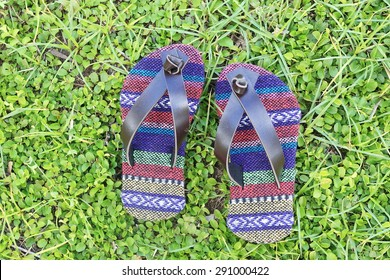 Children's slippers made from  tribal fabric. The backdrop is the grass