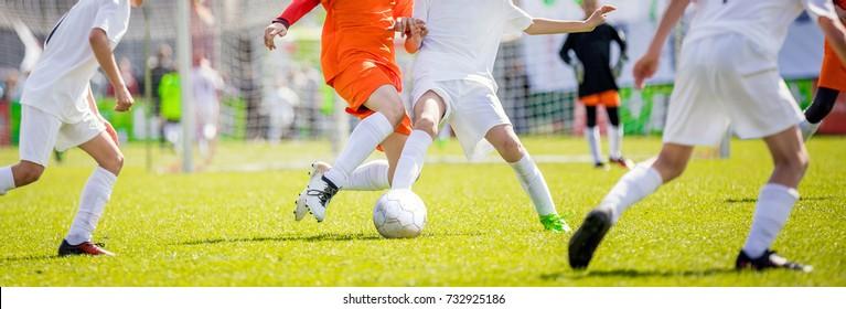 Children's soccer drills. Kids kicking football match on pitch. College soccer class. Running soccer players. Sport education.