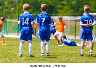 Children's Soccer Match. Kids Playing Soccer Game. Group Of Children In Soccer Team Having Training and Watching Soccer Match. Group of Boys Soccer Players Standing Together and Supporting Team.