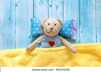 children's soft toy teddy bear in bed with thermometer and pills, take the temperature of a mercury glass . On  blue wooden background   yellow blanket. Playing in hospital.