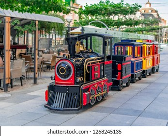 Children's summer attraction locomotive with cars on a city street